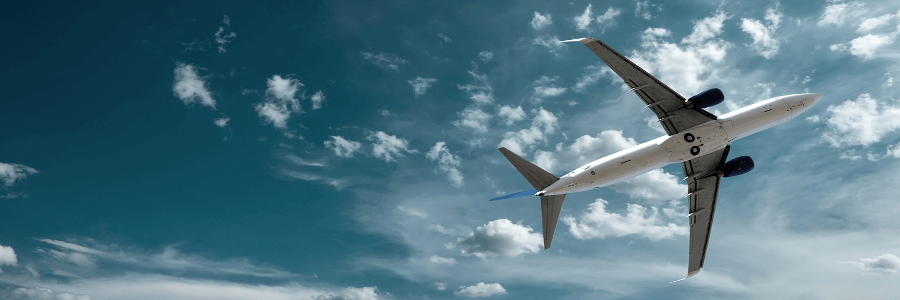 Commercial aircraft pictured flying in the blue sky. This symbolises the aerospace business sector for QCI group