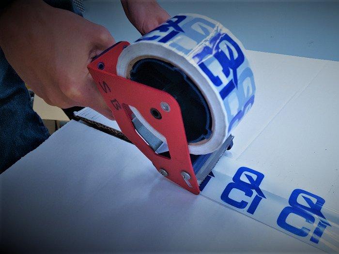 3pl & fulfilment - QCI warehouse operative using a tape gun to seal an aerospace package using QCI tape