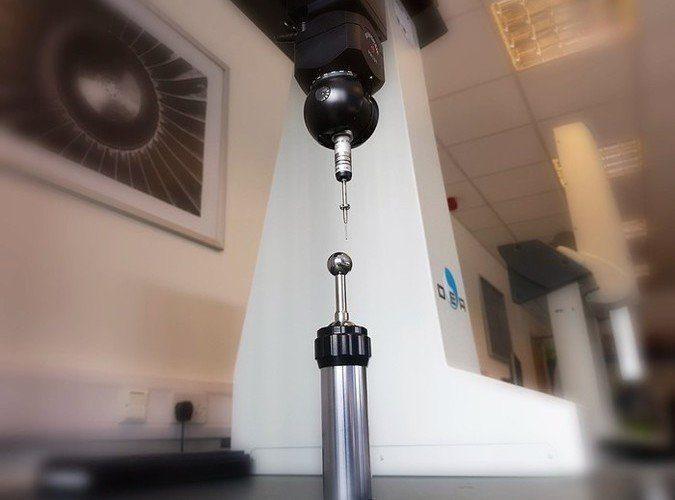 CMM inspection & measurement services - QCI CMM machine conducting calibration of the CMM styli using a CMM artifact