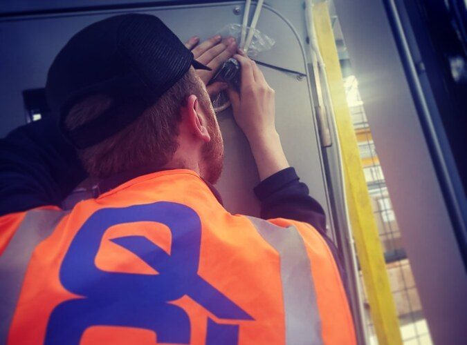 Rail inspector visually checking wiring within a train
